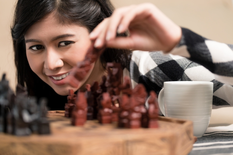 Indonesian woman playing chess setting figure