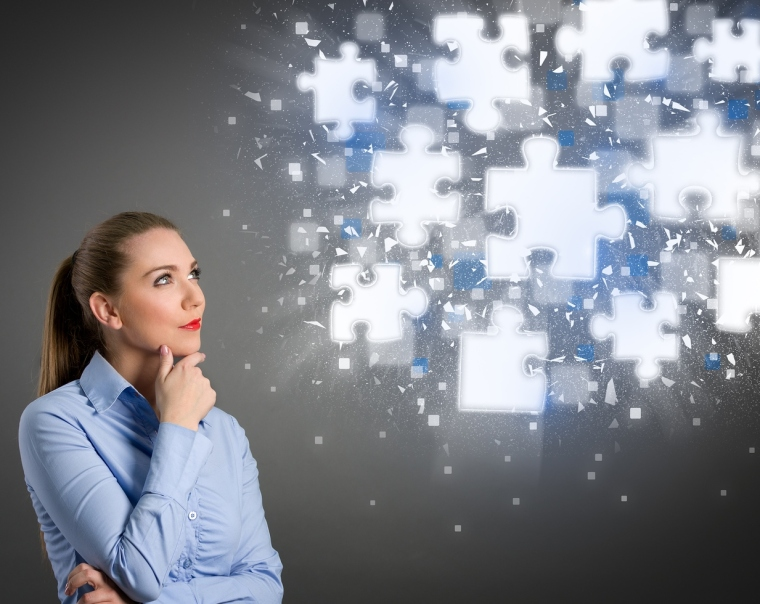 Thinking businesswoman looking at clouds of shining puzzle piece
