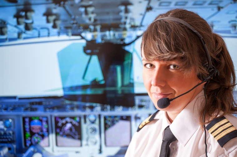 Beautiful woman pilot wearing uniform with epauletes, headset si