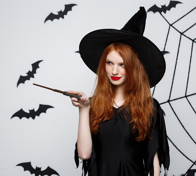 Halloween Concept - Beautiful Witch Playing With Magic Stick On