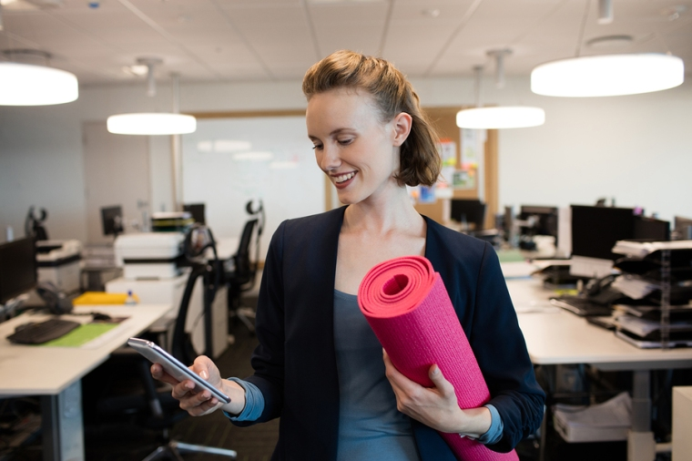 Smiling businesswoman with exercise mat using mobile phone at of