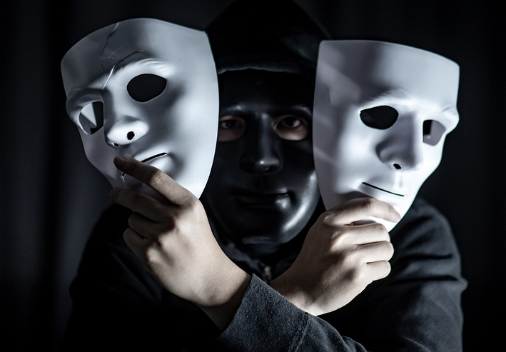 Mystery Hoody Man Wearing Black Mask Holding Two White Masks In
