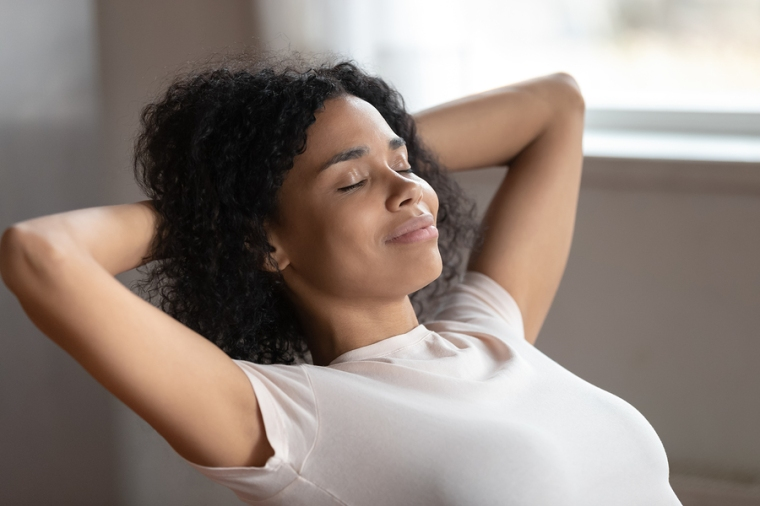 Mixed Race Woman Putting Hands Behind Head Resting Indoors