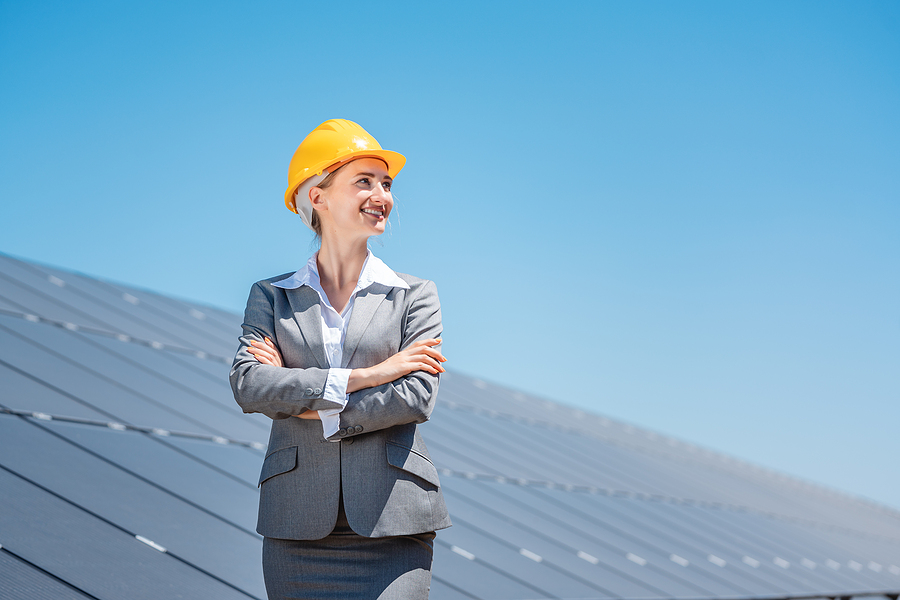 Woman investor in clean energy standing proudly in front of sola