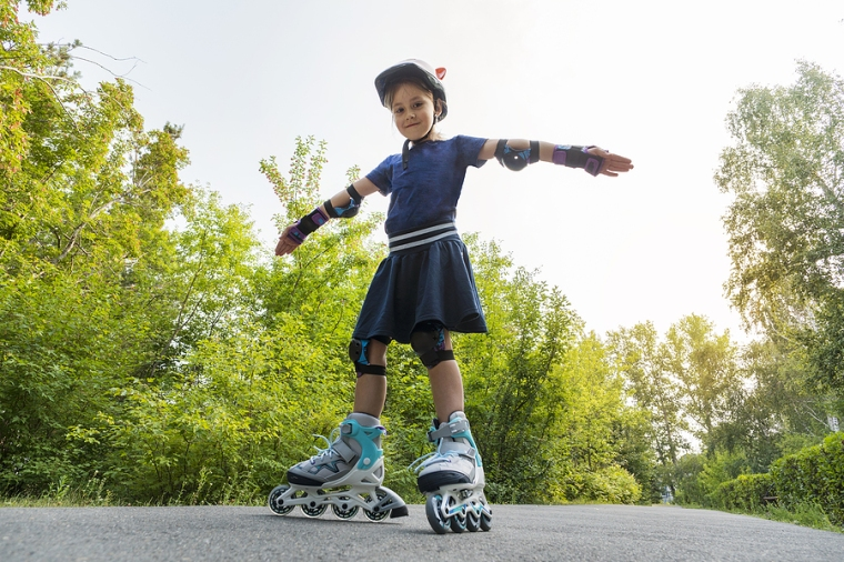 Little Girl On Roller Skates At A Park. A Child Rides On Roller